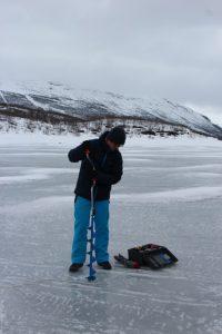 Student drills through lake ice