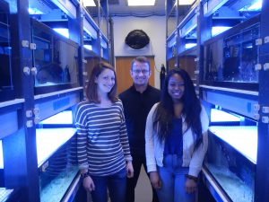 Photo of Tina (left) with other members of her lab. The glowing blue tanks around them all contain anemonefish!